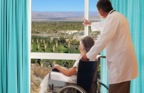Doctor with a patient in a wheelchair in front of a large window