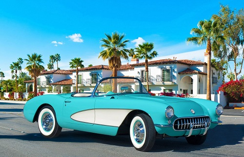 Classic blue car on a street in front of homes and palm trees
